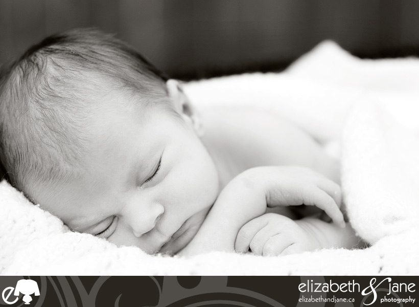 Newborn Photo: Black and white closeup of baby boy sleeping on a white blanket