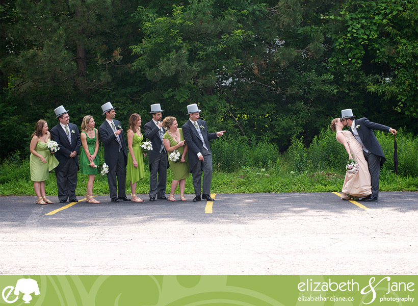 Wedding Photos: photo of the bridal party where they are looking and pointing at the bride and groom who are kissing