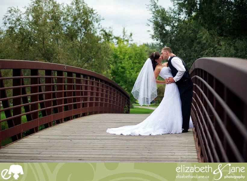 Wedding Photo: couple standing on a bridge kissing