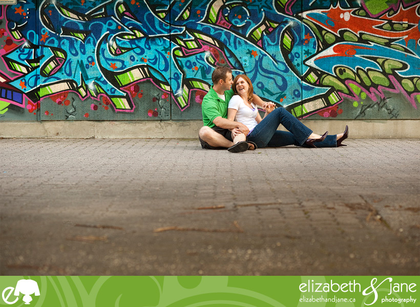 Photo of a couple sitting by a graffiti wall