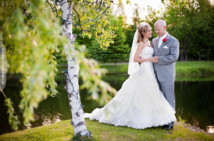 Wedding Photo: bride and groom having a quiet moment together by a pond