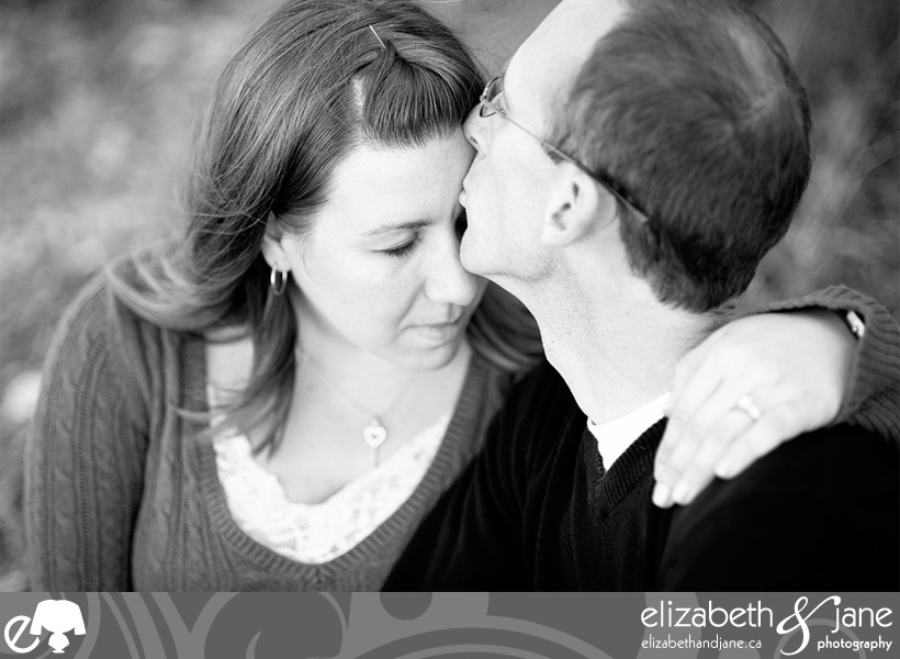 Engagement photo: black and white photo of the groom to be kissing the bride to be