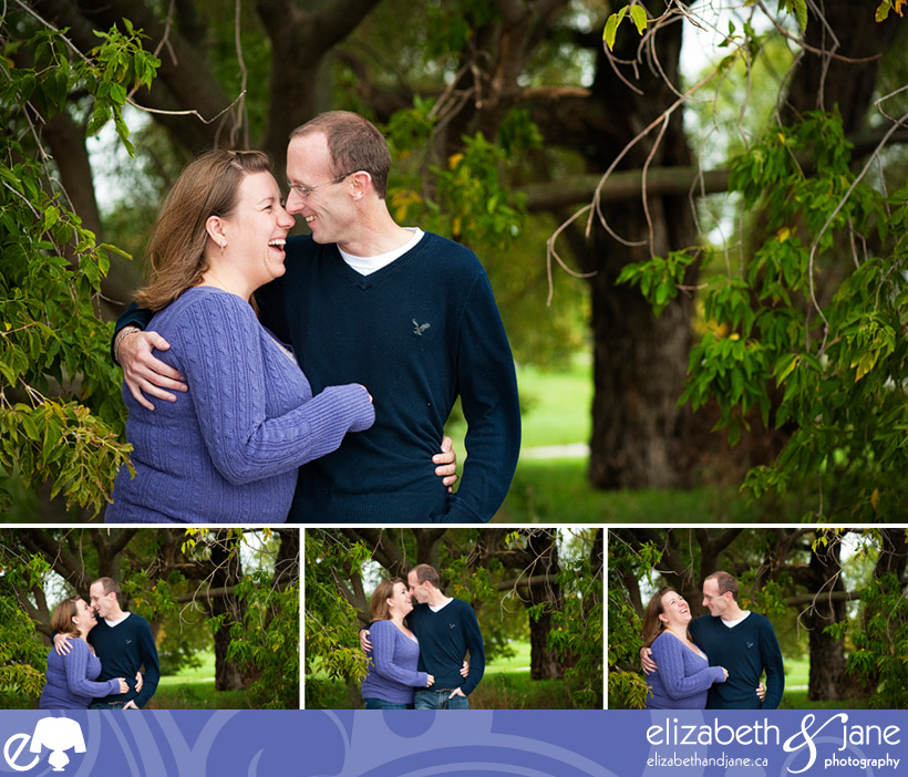 Engagement photo: couple laughing surrounded by trees