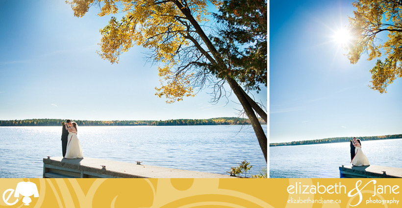 Wedding Photo: bride and groom embracing on a dock with a view of the lake
