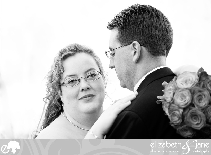Wedding Photo: black and white photo of the bride looking at the camera with the groom looking at her