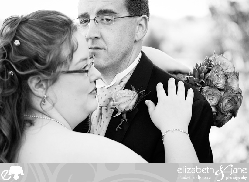 Wedding Photo: black and white photo of the groom looking at the camera and the bride looking off camera