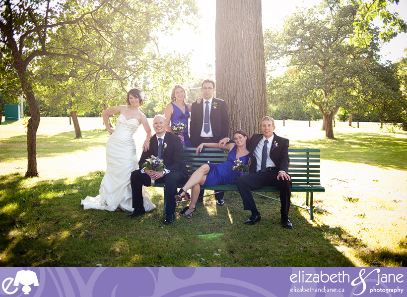 The wedding party sitting on a bench.