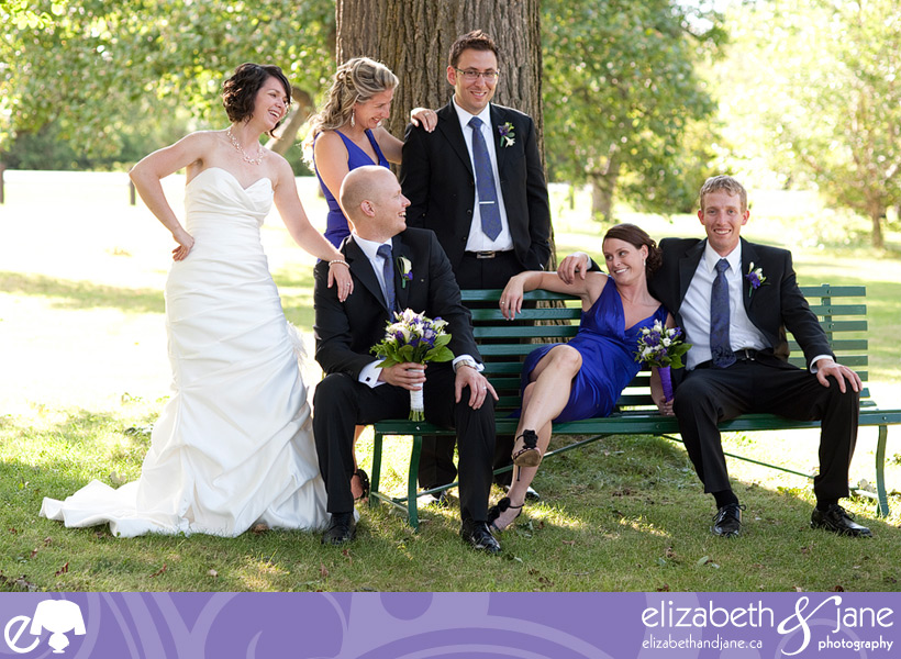 The wedding party sitting on a bench laughing.