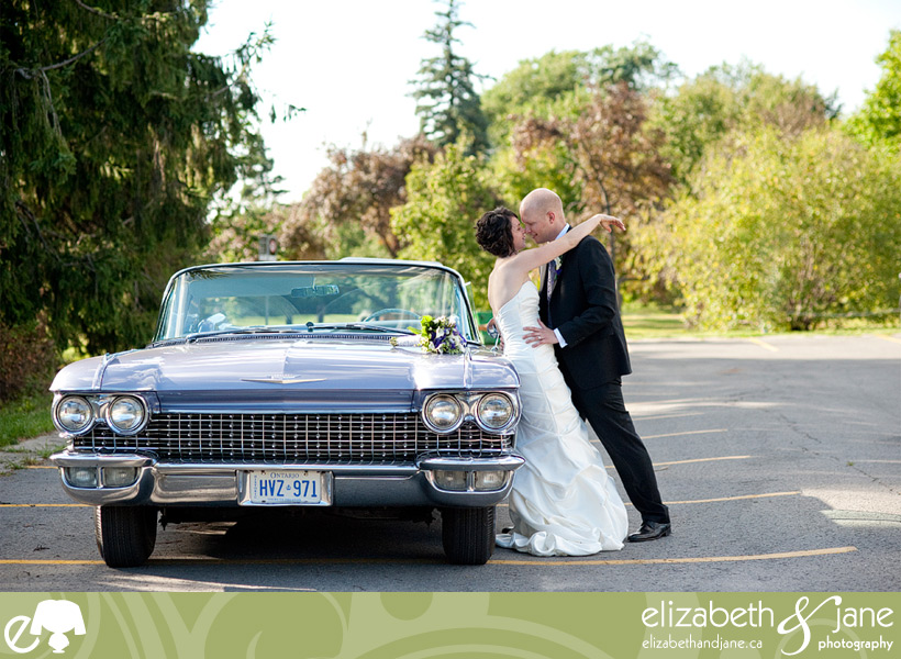 The bride and groom leaning on a vintage car with their noses touching.