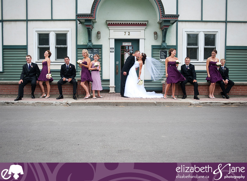 Bridal party standing in a line outside of a building, bride and groom kissing